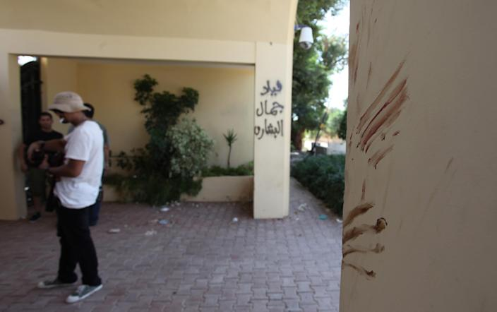"""Bloodstains at the main gate believed to be from one of the American staff members of the U.S. Consulate, after an attack that killed four Americans, including Ambassador Chris Stevens on the night of Tuesday, Sept. 11, 2012, in Benghazi, Libya, Thursday, Sept. 13, 2012. The American ambassador to Libya and three other Americans were killed when a mob of protesters and gunmen overwhelmed the U.S. Consulate in Benghazi, setting fire to it in outrage over a film that ridicules Islam's Prophet Muhammad. Ambassador Chris Stevens, 52, died as he and a group of embassy employees went to the consulate to try to evacuate staff as a crowd of hundreds attacked the consulate Tuesday evening, many of them firing machine-guns and rocket-propelled grenades. Arabic writing reads, """" Villa of Jamal al Beshary"""". which was written by the original owner to protect the property from another attack. (AP Photo/Mohammad Hannon)"""
