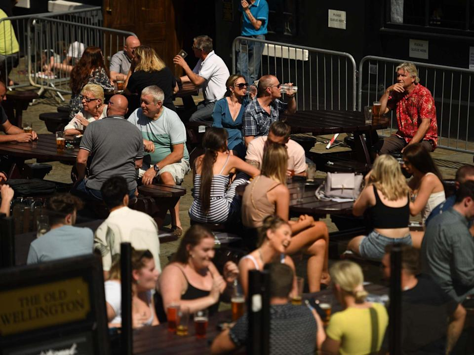 People sit with drinks outside a pub in the centre of Manchester, 31 July 2020: Oli Scarff/AFP via Getty Images