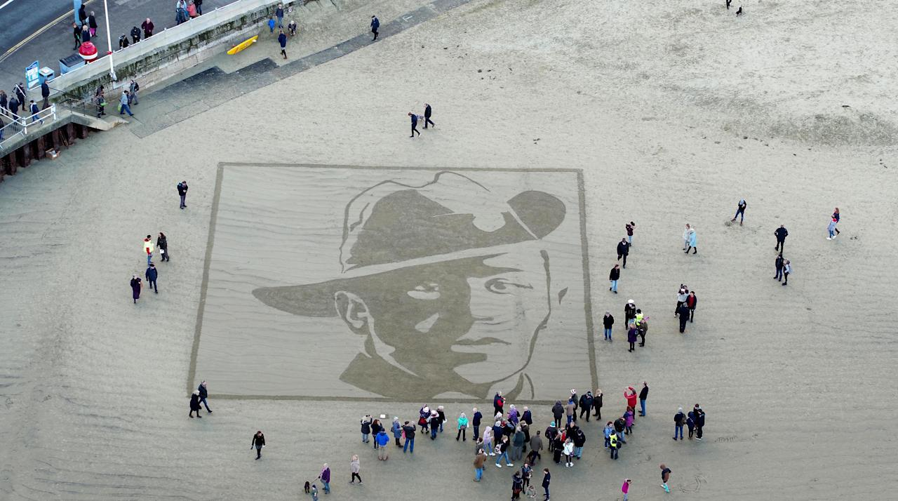 <p>The face of Private Stanley McDougall etched onto the shore at Weymouth Beach, Dorset, as part of Pages of the Sea event. (Finbarr Webster/REX) </p>
