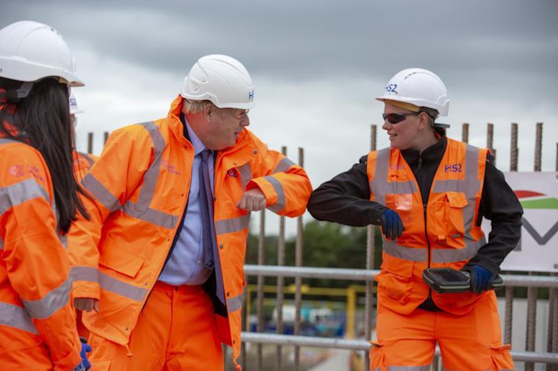 Prime Minister Boris Johnson (centre left) greets a worker during a visit to the HS2 Solihull Interchange building site in the West Midlands to mark the formal start of construction on HS2.