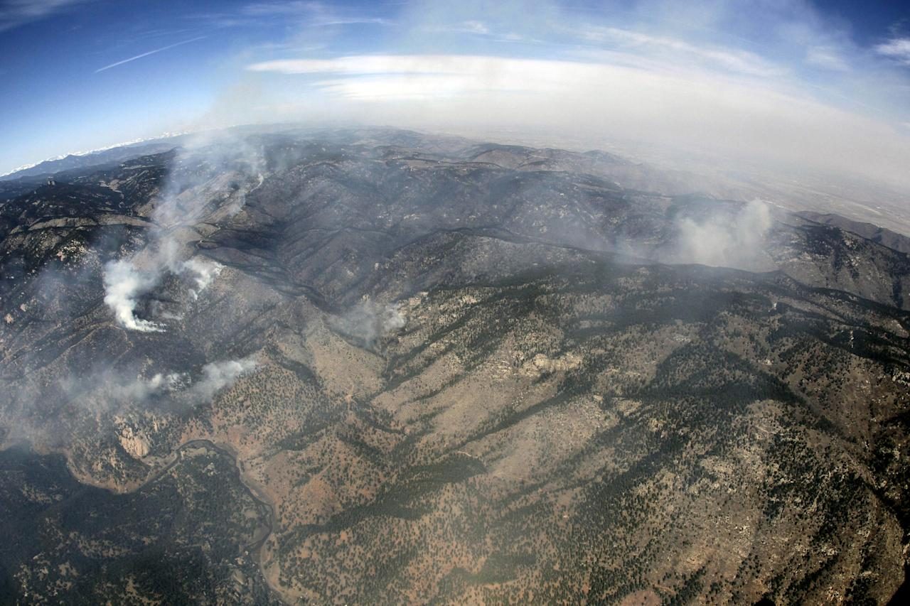 In this aerial photograph made using a fisheye lens, the Lower North Fork Wildfire burns near the foothills community of Conifer, Colo., southwest of Denver on Tuesday, March 27, 2012. Firefighters are now able to actively battle the blaze on the ground that started on Monday and has already destroyed at least 16 homes in the rugged terrain. (AP Photo/David Zalubowski)