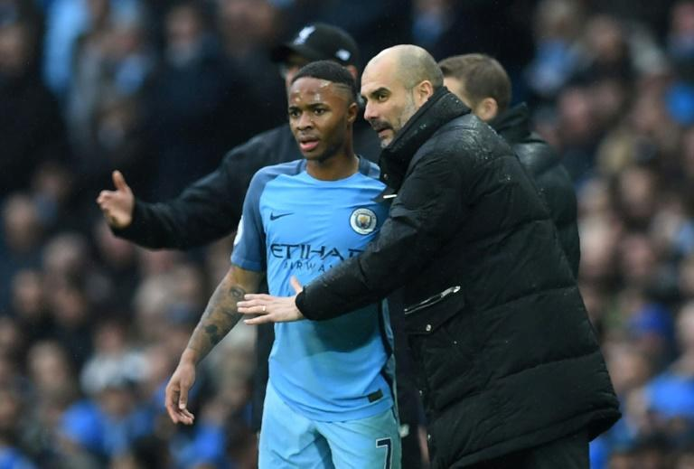 Manchester City's manager Pep Guardiola (R) speaks to midfielder Raheem Sterling during their English Premier League match against Liverpool, at the Etihad Stadium in Manchester, on March 19, 2017