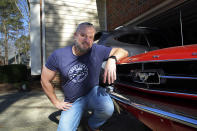 Steve Bock kneels beside his 1965 Ford Mustang at his home in Apex, N.C., on Friday, March 5, 2021. He recently bought a Subaru Outback, but would like to have an electric or hybrid car if the prices ever come down enough. Opinion polls show that most Americans would consider an EV if it cost less, if more charging stations existed and if a wider variety of models were available. (AP Photo/Allen G. Breed)