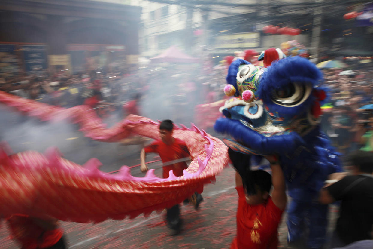 Dragon and lion dancers perform amidst exploding firecrackers in front of a business establishment in celebration of the Chinese Lunar New Year, Saturday, Jan. 28, 2017, in the Chinatown area of Manila, Philippines. This year is the Year of the Rooster on the Chinese lunar calendar. (AP Photo/Bullit Marquez)