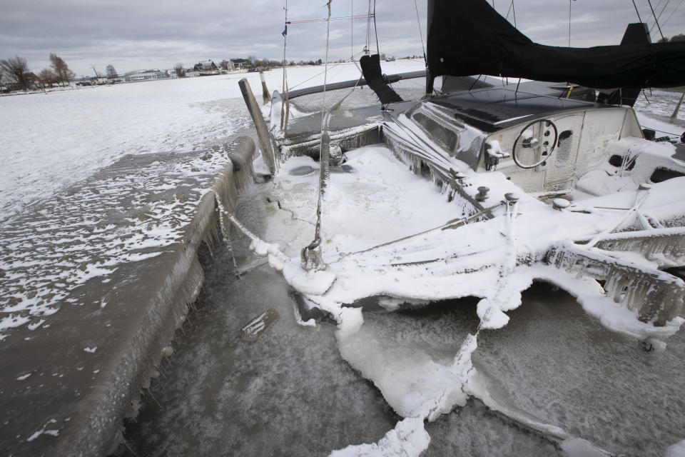 A catamaran, battered and broken on the dock by strong winds and ice, is seen in the marina of Monnickendam, Netherlands, Tuesday, Feb. 9, 2021. With freezing temperatures forecast for more than a week in the Netherlands, ice fever is sweeping the nation, offering a welcome respite from grim coronavirus news while also creating a challenge for authorities trying to uphold social distancing measures. (AP Photo/Peter Dejong)