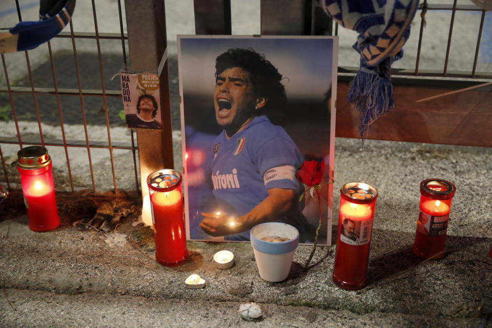 Candles are placed next to a picture of soccer legend Diego Maradona outside the San Paolo Stadium in Naples, Italy, Wednesday, Nov. 25, 2020. Diego Maradona has died. The Argentine soccer great was among the best players ever and who led his country to the 1986 World Cup title before later struggling with cocaine use and obesity. He was 60. (AP Photo/Alessandra Tarantino)