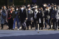 People wearing protective masks to help curb the spread of the coronavirus walk along pedestrian crossings in the Shibuya area of Tokyo Thursday, Jan. 7, 2021. The Japanese capital confirmed more than 2000 new coronavirus cases on Thursday. (AP Photo/Eugene Hoshiko)
