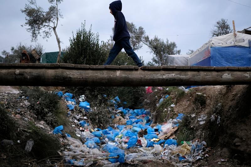 A migrant boy walks over discarded garbage outside the Moria refugee camp on the northeastern Aegean island of Lesbos, Greece: AP