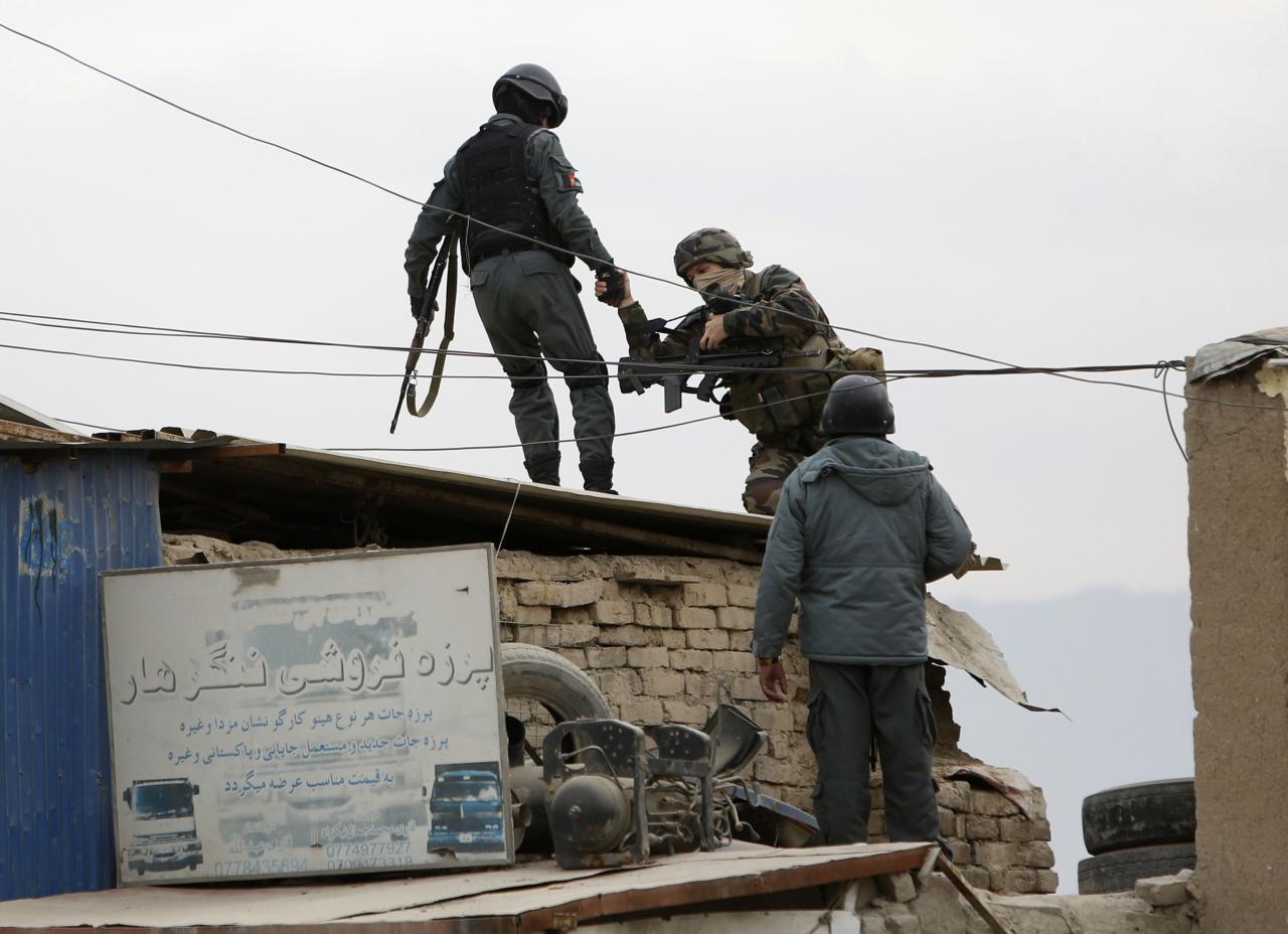 An Afghan policeman (L) helps a serviceman from International Security Assistance Force (ISAF) at the site of a bomb attack in Kabul December 27, 2013. A suspected suicide bomber attacked a foreign military convoy on the eastern outskirts of the Afghan capital, Kabul, on Friday, killing at least three foreign soldiers, police and the NATO-led ISAF said. REUTERS/Mohammad Ismail (AFGHANISTAN - Tags: CIVIL UNREST MILITARY POLITICS)