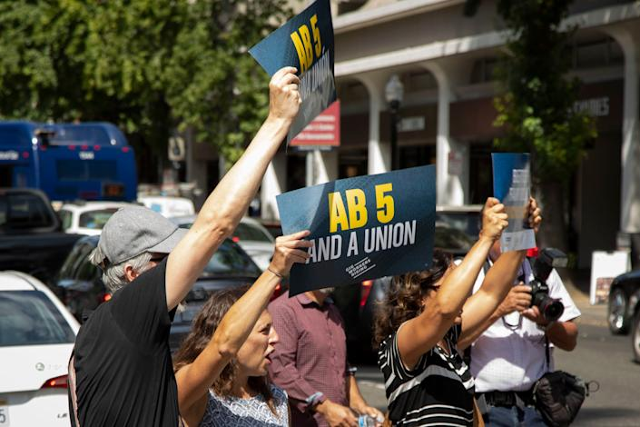 Lyft and Uber drivers rally in support of AB 5 on Wednesday, Aug. 28, 2019, in Sacramento, Calif.