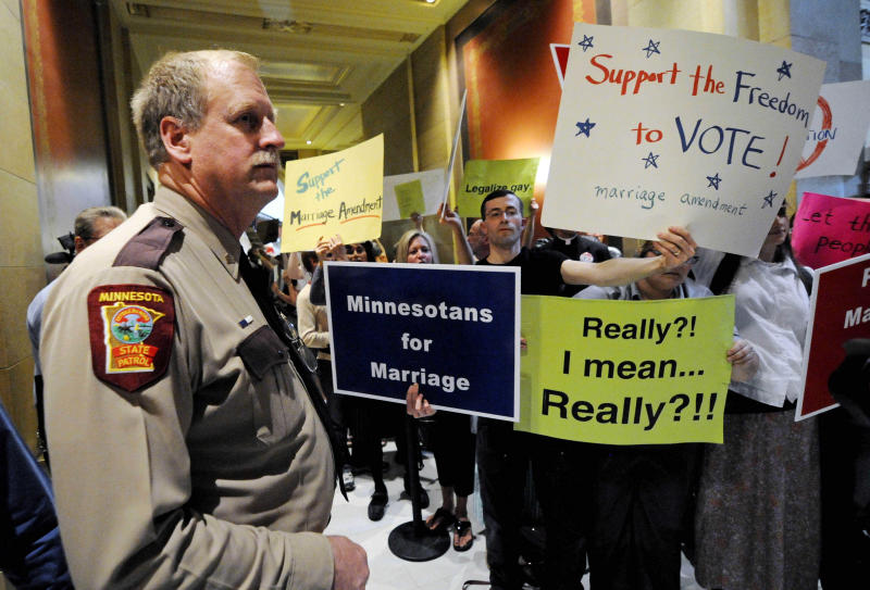 FILE - In this May 19, 2011 file photo, a state trooper stands by as demonstrators on both sides of the gay marriage issue gather outside the Minnesota House in St. Paul, Minn. Poll after poll shows public support for same-sex marriage steadily increasing, to the point where it's now a majority viewpoint. Yet in all 32 states where gay marriage has been on the ballot, voters have rejected it. It's possible the streak could end in November 2012, when Maine, Maryland, Minnesota and Washington state are likely to have closely contested gay marriage measures on their ballots. For now, however, there remains a gap between the national polling results and the way states have voted. (AP Photo/Jim Mone, File)