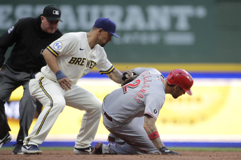 Cincinnati Reds' Nick Castellanos (2) steals second base past the tag of Milwaukee Brewers' Jace Peterson, center, during the second inning of a baseball game Monday, June 14, 2021, in Milwaukee. (AP Photo/Aaron Gash)