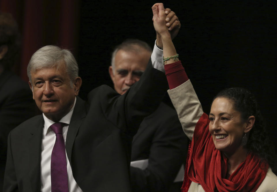 Presidential hopeful Andres Manuel Lopez Obrador, left, and Claudia Sheinbaum, coordinator of the Morena political party, hold hands at an event at the National Auditorium in Mexico City, Monday, Nov. 20, 2017. Lopez Obrador, making his third bid for Mexico's presidency, laid out his platform for next year's presidential elections. (AP Photo/Marco Ugarte)