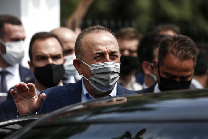 """Turkish Foreign Minister Mevlut Cavusoglu, center, leaves a muslim cemetery at Komotini town, in northeastern Greece, Sunday, May 30, 2021. Greece's prime minister said Friday his country is seeking improved ties with neighbor and longtime foe Turkey, but that the onus is on Turkey to refrain from what he called """"provocations, illegal actions and aggressive rhetoric."""" (AP Photo/Giannis Papanikos)"""