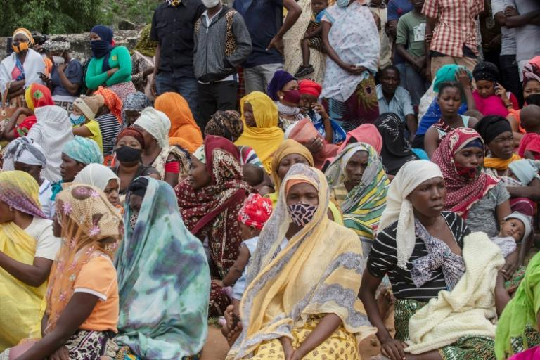 Families wait outside the port of Pemba to leave the town