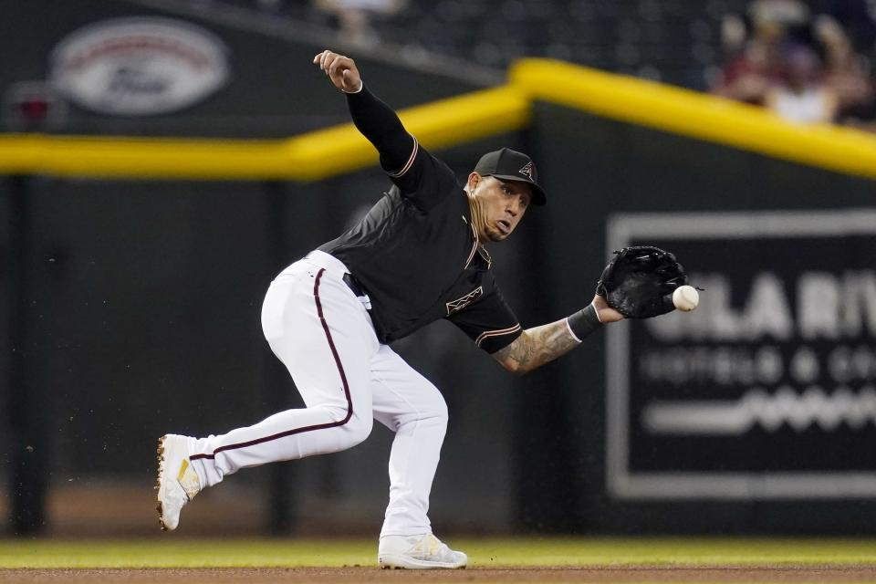 Arizona Diamondbacks third baseman Asdrubal Cabrera reaches out to field a grounder hit by Cincinnati Reds' Nick Castellanos, before throwing to first base for the out during the first inning of a baseball game Saturday, April 10, 2021, in Phoenix. (AP Photo/Ross D. Franklin)