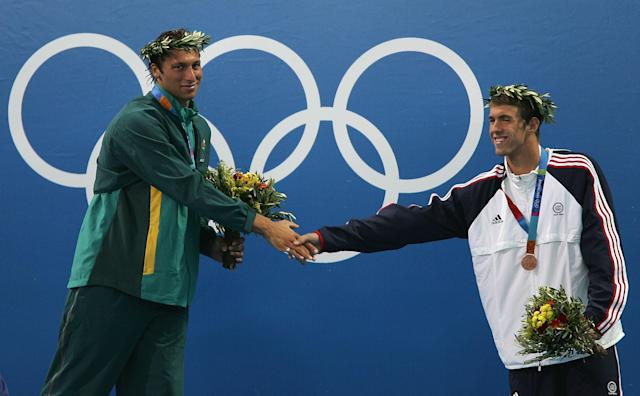 ATHENS - AUGUST 16: Bronze medalist Michael Phelps of USA greets gold medalist Ian Thorpe of Australia as they stand on the podium during the medal ceremony for the men's swimming 200 metre freestyle event on August 16, 2004 during the Athens 2004 Summer Olympic Games at the Main Pool of the Olympic Sports Complex Aquatic Centre in Athens, Greece.. Pieter Van Den Hoogenband finshed third. (Photo by Stuart Hannagan/Getty Images)