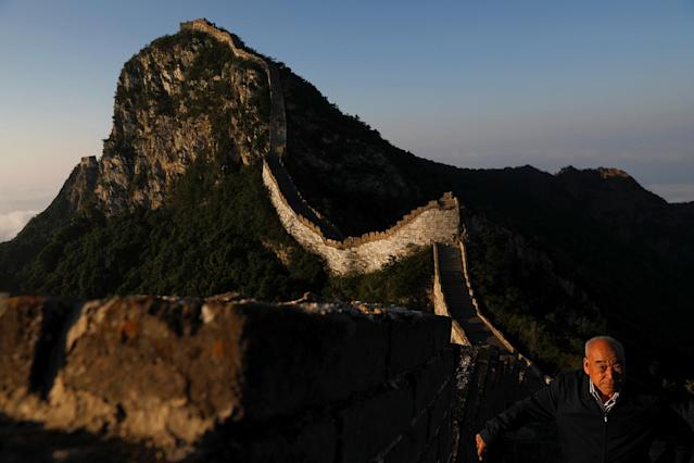 <p>Cheng Yongmao, the engineer in charge of the reconstruction project on the Jiankou section of the Great Wall, looks as the sun rises over the wall, located in Huairou District, north of Beijing, China, June 7, 2017. (Photo: Damir Sagolj/Reuters) </p>