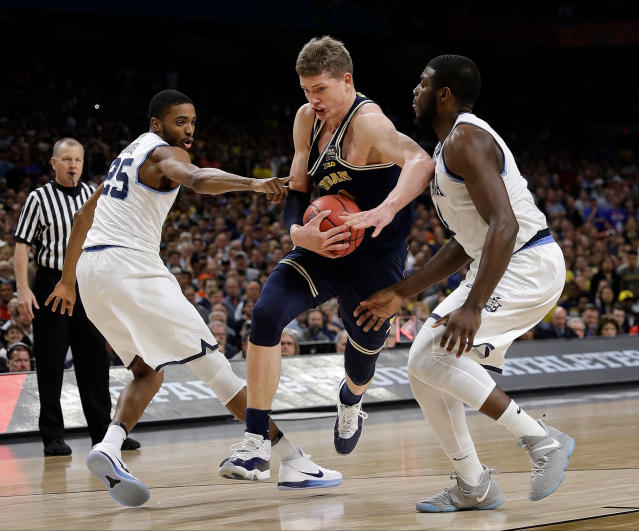 Michigan's Moritz Wagner (13) drives between Villanova's Mikal Bridges (25) and Eric Paschall during the first half in the championship game of the Final Four NCAA college basketball tournament, Monday, April 2, 2018, in San Antonio. (AP Photo/David J. Phillip)