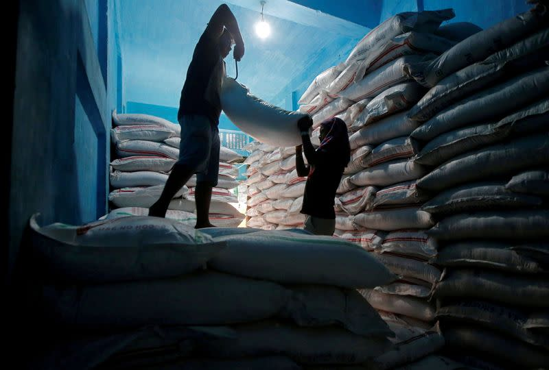 FILE PHOTO: Labourers lift a sack filled with sugar to load it onto a handcart at a wholesale market in Kolkata