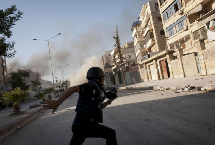 A reporter, identified as Medyan Dairieh, runs after being injured in the leg, across a sniper corridor during heavy fighting in the Saif al-Dawla district of Aleppo, Syria, on August 24, 2012 (AFP Photo/James Lawler Duggan)