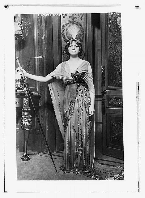 """<p>Cooper radiates turn-of-the-century chic with her silver headdress and beaded gown boasting a gauzy train. This 1913 photo reflects her newly found success after playing Muriel Pym in the play """"Milestones.""""</p>"""