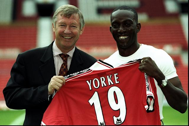 20 Aug 1998: Dwight Yorke of Trinidad and Tobago receives his shirt from manager Alex Ferguson after completing his 12 million pound transfer to Manchester United at Old Trafford in Manchester, England. \ Mandatory Credit: Allsport UK /Allsport