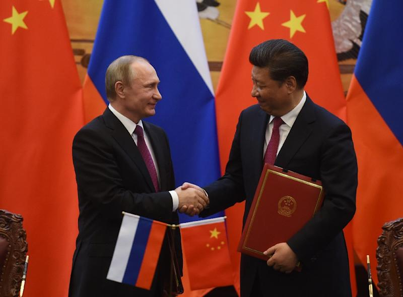 Analysts say Xi Xinping sees an enviable model in Russia's Vladimir Putin, who has successfully kept power for well over a decade by bouncing between the offices of president and prime minister (AFP Photo/Greg Baker)