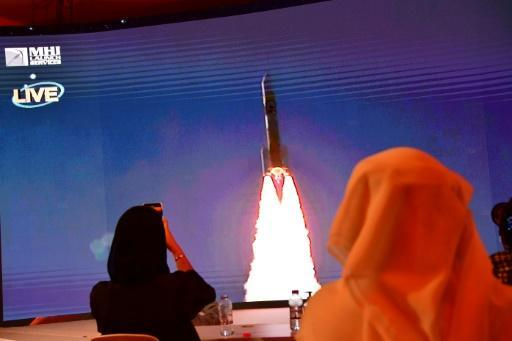 """Staff at the Mohammed Bin Rashid Space Centre in Dubai follow the broadcast launch of the """"Hope"""" Mars probe on a large streen"""