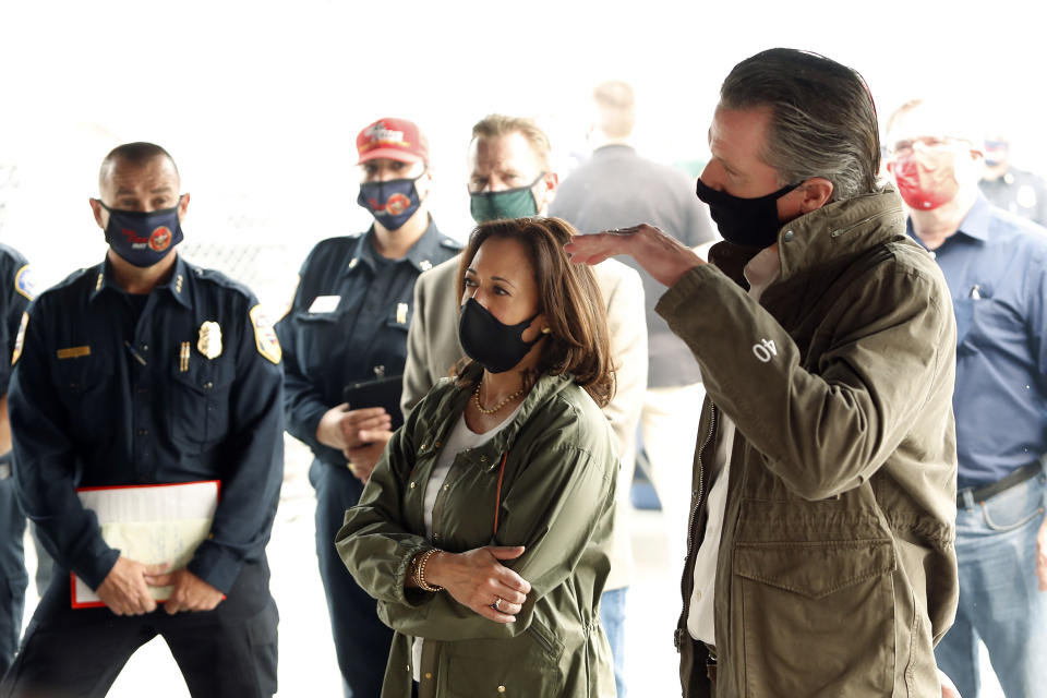 Calif. Gov. Gavin Newsom, right, and Democratic vice presidential candidate Sen. Kamala Harris, D-Calif., are briefed on the Creek Fire at Pine Ridge Elementary, Tuesday, Sept. 15, 2020 in Auberry, Calif. (AP Photo/Gary Kazanjian)
