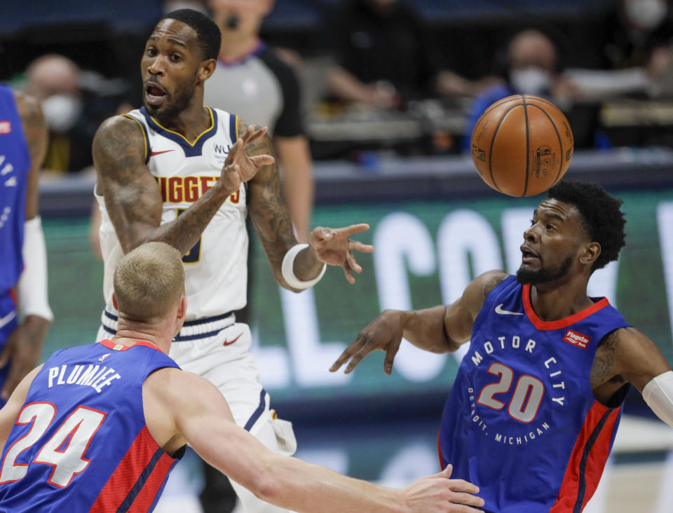 Denver Nuggets forward Will Barton, left, passes between Detroit Pistons center Mason Plumlee (24) and guard Josh Jackson (20) in the first quarter of an NBA basketball game in Denver, Tuesday, April 6, 2021. (AP Photo/Joe Mahoney)