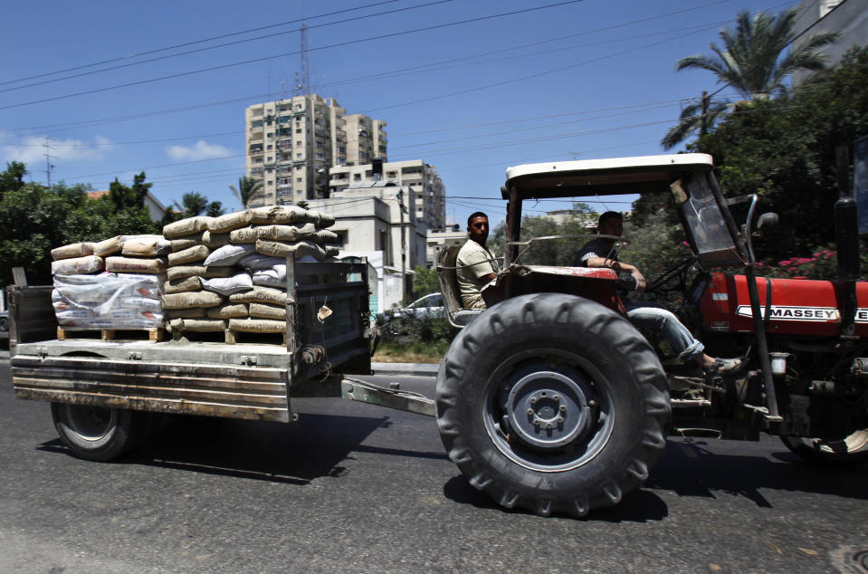 In this photo taken on Wednesday, July 31, 2013, Palestinian workers ride a tractor towing cement bags for construction in Gaza City. Regime change in Egypt has cost the Hamas rulers of Gaza their most important foreign ally, and ordinary Palestinians are being caught up in the animosity. Many Gazans were laid off after Egypt closed the territory's border, and Palestinians living in Egypt are keeping a low profile for fear of being targeted in the backlash against Hamas. (AP Photo/Adel Hana)
