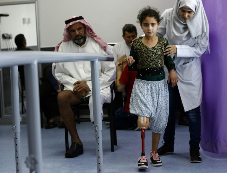 Amani, a 10-year-old amputee, is helped as she tries to walk with her new artificial limb at the Syrian Arab Red Crescent facility, in Damascus on July 15, 2018