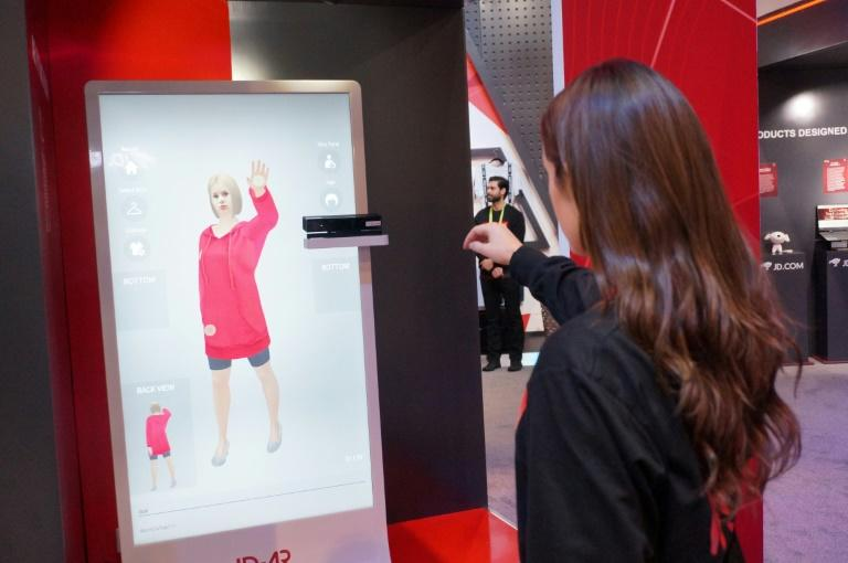 An employee of Chinese tech giant JD.com shows an augmented reality system that allows customers to virtually try on clothing at shops, part of the high-tech retail marketplace at the 2019 Consumer Electronic Show in Las Vegas