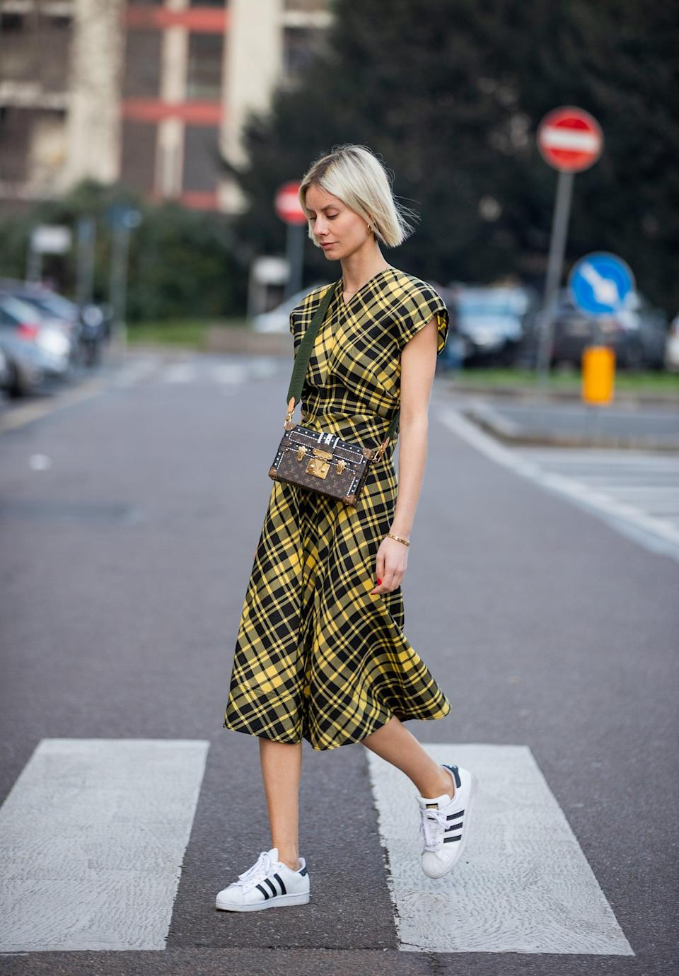 <p>A classic sneaker makes this plaid dress feel sporty.</p>