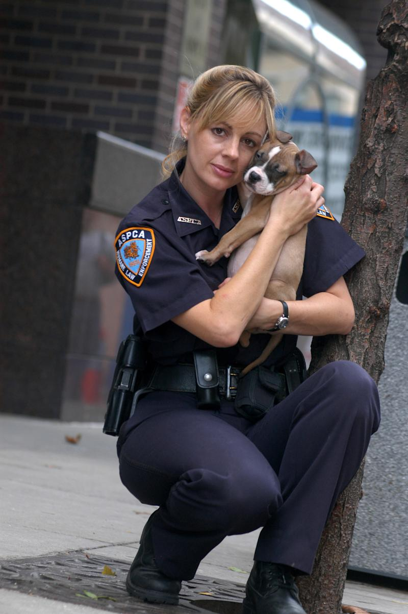 """FILE -This 2004 photo provided by Animal Planet shows investigator Annemarie Lucas of the Humane Law Enforcement division of the American Society for the Prevention of Cruelty to Animals with a rescued dog in New York. ASPCA agents wore uniforms, flashed badges, carried guns, traveled in blue-and-white squad cars, and for years starred in """"Animal Precinct,"""" as did Lucas, but as of this month, the ASPCA laid off almost all of its 18 law enforcement agents and is now leaving those responsibilities solely to the New York City Police Department. (AP Photo/Animal Planet, Laura Pedrick)"""