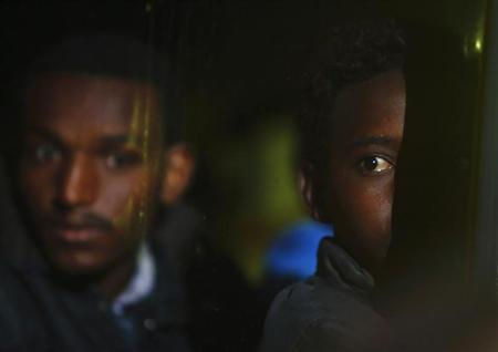 African would-be immigrants look on as they sit in a police bus after disembarking from a patrol boat at the Armed Forces of Malta Maritime Squadron base at Haywharf, in Valletta's Marsamxett Harbour
