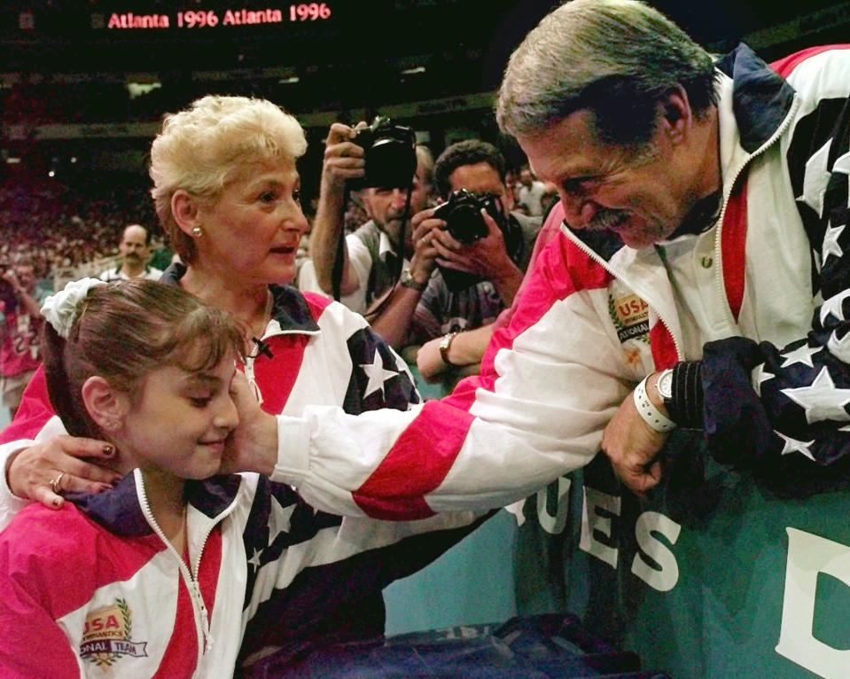 FILE - In this July 23, 1996, file photo, Bela Karolyi, right, congratulates Dominique Moceanu, left, after the United States captured the gold medal in the women's team gymnastics competition at the Centennial Summer Olympic Games in Atlanta. United States team coach Martha Karolyi, center, looks on.(AP Photo/Amy Sancetta, File)