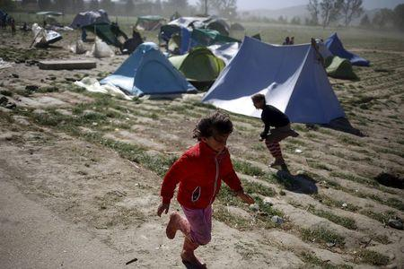 Children run for cover during heavy winds at a makeshift camp for migrants and refugees at the Greek-Macedonian border near the village of Idomeni, Greece, April 20, 2016. REUTERS/Stoyan Nenov