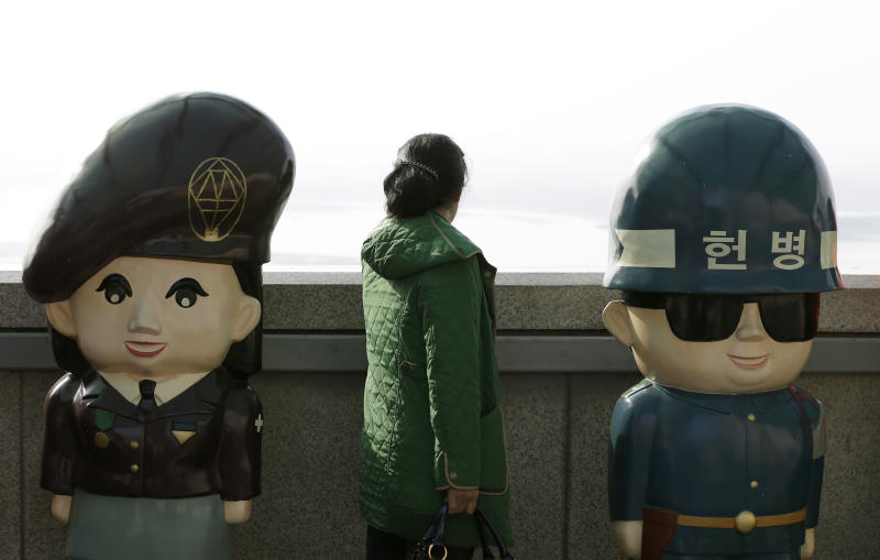 A woman looks at North Korean territory next to dolls of South Korean soldiers at the unification observation post near the border village of Panmunjom, which has separated the two Koreas since the Korean War, in Paju, north of Seoul, South Korea, Monday, April 15, 2013. Foreign governments have been struggling to assess how seriously to take North Korea's recent torrent of rhetoric — including warnings of possible nuclear war — as it expresses its anger over continuing U.S.-South Korea military maneuvers just across the border. Officials in South Korea, the United States and Japan say intelligence indicates that North Korean officials, fresh off an underground nuclear test in February, are ready to launch a medium-range missile. (AP Photo/Lee Jin-man)
