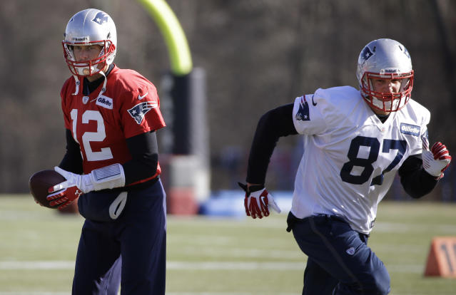 New England Patriots quarterback Tom Brady (12) walks through a play with tight end Rob Gronkowski (87) during a stretching and drills session before practice begins at the NFL football team's facility in Foxborough, Mass., Wednesday, Nov. 20, 2013. Tom Brady and the Patriots will play Peyton Manning and the Denver Broncos Sunday night in Foxborough. (AP Photo/Stephan Savoia)