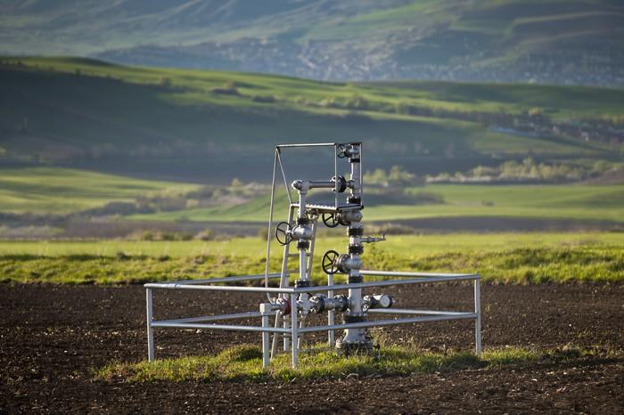 A natural gas wellhead in the middle of a field.