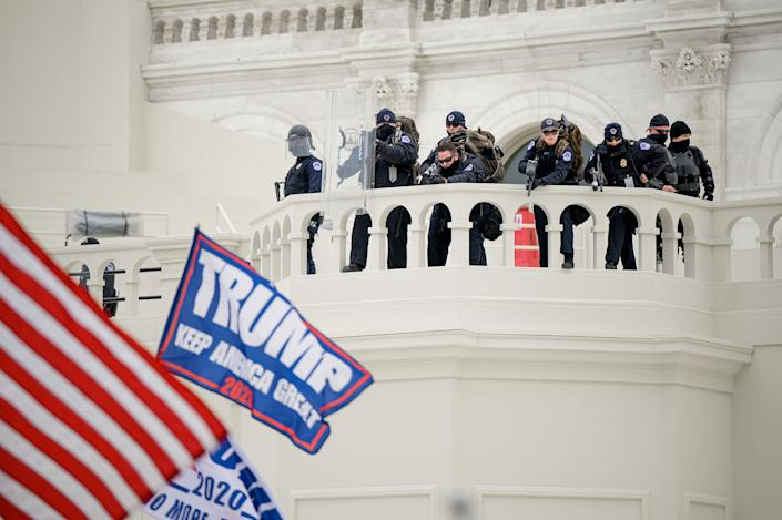 """Capitol police officers take position as a pro-Trump mob attempts to enter the Capitol Building.<span class=""""copyright"""">Joel Marklund—Reuters</span>"""