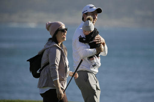 Nick Taylor, of Canada, walks off the 18th green of the Pebble Beach Golf Links with his wife Andie and son Charlie after winning the AT&T Pebble Beach National Pro-Am golf tournament Sunday, Feb. 9, 2020, in Pebble Beach, Calif. (AP Photo/Eric Risberg)