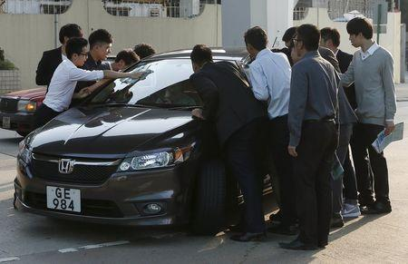 Property sales agents stop a car as they approach a potential client outside a model flat in Hong Kong March 20, 2015.  REUTERS/Bobby Yip
