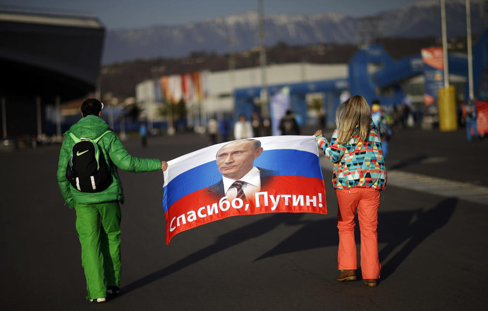 """FILE - In this Feb. 23, 2014 file photo Veleriya Obarevich, right, and Yan Shamilov carry a Russian flag with the message """"Thank you, Putin!"""" written across it in Russian through Olympic Park ahead of the 2014 Winter Olympics closing ceremony in Sochi, Russia. Russia was banned Thursday Dec. 17, 2020 from using its name, flag and anthem at the next two Olympics or at any world championships for the next two years. The Court of Arbitration for Sport's ruling also blocked Russia from bidding to host major sporting events for two years. (AP Photo/David Goldman, file)"""