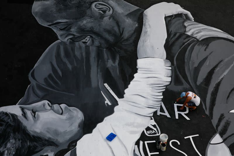 A man polishes the mural in memory of Kobe Bryant and his daughter Gianna, painted hours after they died in a helicopter crash, on the basketball court of a housing tenement in Taguig City, Metro Manila