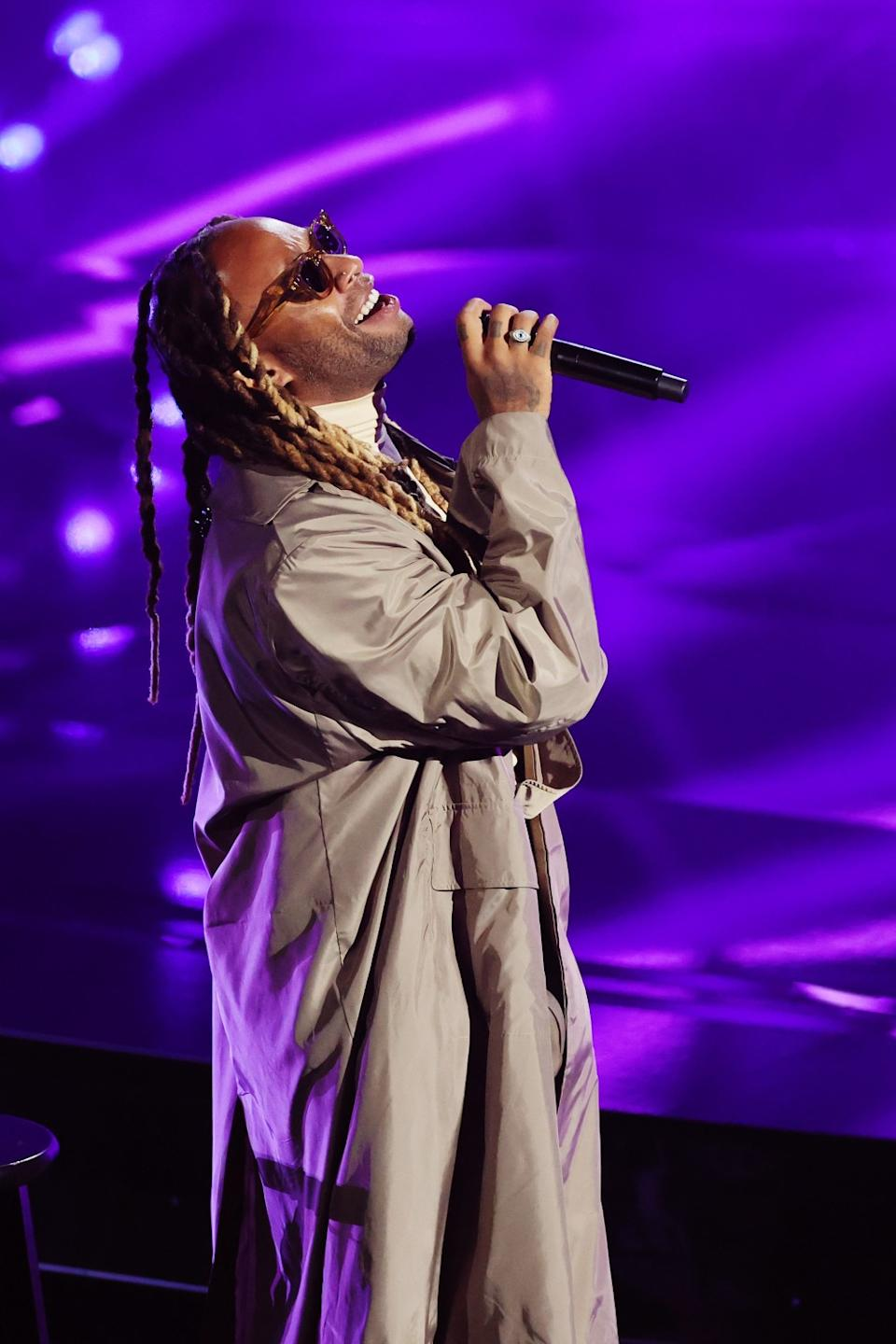 Ty Dolla Sign, in sunglasses and a long tan duster, sings into the microphone.