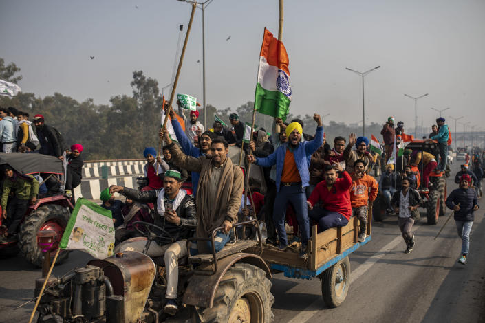 Protesting farmers ride tractors and shout slogans as they march to the capital breaking police barricades during India's Republic Day celebrations in New Delhi, India, Tuesday, Jan.26, 2021. Tens of thousands of farmers drove a convoy of tractors into the Indian capital as the nation celebrated Republic Day on Tuesday in the backdrop of agricultural protests that have grown into a rebellion and rattled the government. (AP Photo/Altaf Qadri)