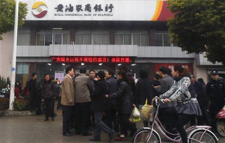 People gather in front of a branch of Rural Commercial Bank of Huanghai in Yancheng, Jiangsu province, March 26, 2014. REUTERS/Carlos Barria